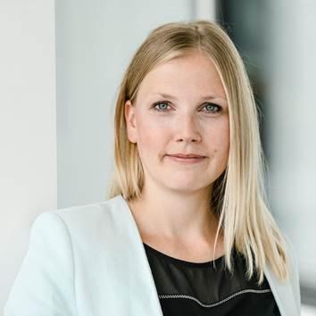 Angela Ditter: junge Frau, mit halblangen, blonden Haaren, in hellblauem Blazer und schwarzem Shirt, lächelt