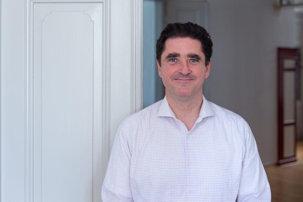 Bernhard Böhm: Mann mit dunklen Haaren, in weißem Hemd vor Zimmertür stehend, lächelt